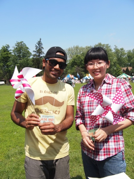 Shashi Bangera (left) and Xiaolu Yang (right) volunteering at the Multicultural Festival in 2013, helping kids make pin-wheels in Victoria Park.