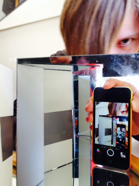 Close up of one of the Youth Council members taking a photograph inside a mirror box.